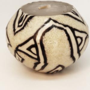 bougie ronde beige avec un motif ethnique noir