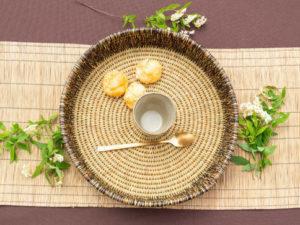 Plateau fait main en fibre naturelle posé sur un chemin de table