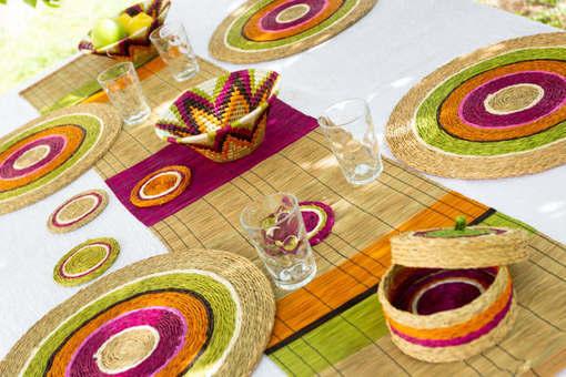table en extérieur décorée avec des sets, un chemin de table et panières