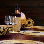 table décorée avec des sets ronds, panière, verres et porte-bouteille
