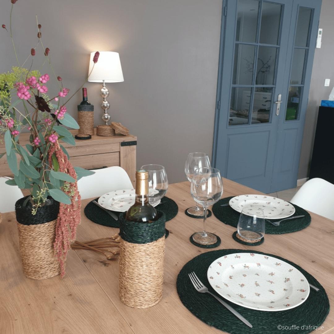 Table mise avec des sets de tables, porte-bouteille et verres